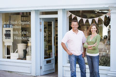 Couple standing in front of organic food store Stock Images