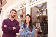 Couple standing in front of a shop window Stock Images