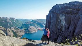 A couple standing in front of teh famous PReikestolen rock in Norway. Fjord in the background royalty free stock photos