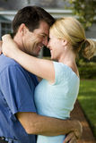 Couple standing on the garden path outside their new home, hugging Stock Image