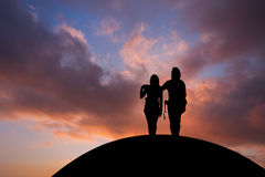 Couple standing on hill in sunset sky Stock Images