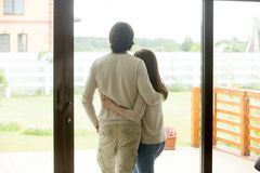 Couple standing at home, embracing looking outside, rear view. Couple standing at home, embracing looking outside through glass door of modern new house with stock photos