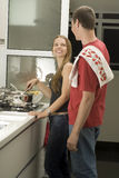 Couple Standing in Kitchen Cooking - Vertical Stock Image