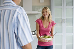Couple standing in kitchen, focus on woman holding salad bowl in background, smiling. Couple standing in kitchen, focus on women holding salad bowl in background Royalty Free Stock Photo