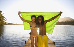 Couple standing on lake jetty, arms around each other, holding aloft green towel, smiling, front view, portrait Royalty Free Stock Photo