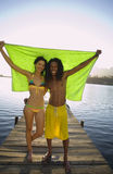 Couple standing on lake jetty, arms around each other, holding aloft green towel, smiling, front view, portrait Stock Photo