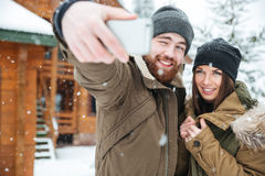 Couple standing and making selfie in snowy weather stock photos