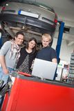 Couple standing with mechanic using laptop stock photography