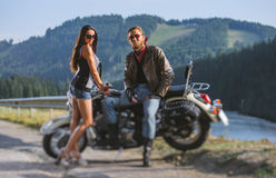 Couple standing by a motorbike. Handsome biker wearing leather jacket leather gloves and boots and young beautiful sexy women wearing shorts. Summer day in the Stock Image