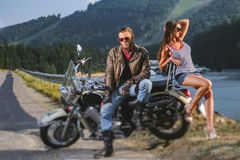 Couple standing by a motorbike. Couple sitting on a motorbike. Handsome men wearing leather jacket, leather gloves and boots and young beautiful sexy girl Royalty Free Stock Photos