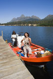 Couple standing in motorboat beside lake jetty, woman releasing rope from mooring post, smiling, portrait Royalty Free Stock Photos