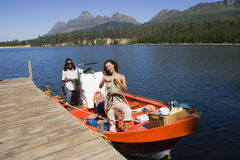 Couple standing in motorboat beside lake jetty, woman releasing rope from mooring post, smiling, portrait Stock Images