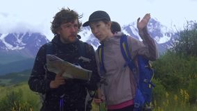 Multiethnic сouple standing on a mountain path looking at a map while standing on a mountain path. Couple standing on a mountain path looking at a map while stock footage