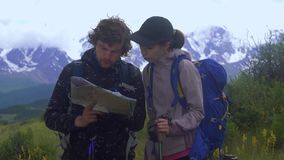 Multiethnic сouple standing on a mountain path looking at a map while standing on a mountain path. Couple standing on a mountain path looking at a map while stock video