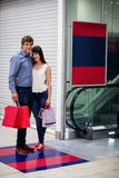 Couple standing near escalator in shopping mall. Couple with shopping bag standing near escalator in shopping mall Royalty Free Stock Photos