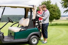Couple standing near the golf cart. Golfing couple getting their golf clubs out of the golf cart royalty free stock photos