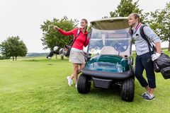 Couple standing near golf cart. Smiling couple with golf kit standing near golf cart royalty free stock image