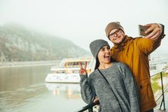 Couple standing near river boat with mountain on bckground. In fog Stock Image