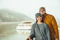 Couple standing near river boat with mountain on bckground. In fog Royalty Free Stock Photos