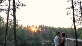 Couple standing near a river in the forest stock video footage