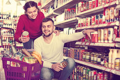 Couple standing near shelves with canned goods at store Royalty Free Stock Images