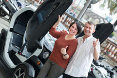 Couple standing near twizy electric Royalty Free Stock Images
