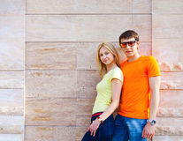 Couple standing near the wall outdoors Royalty Free Stock Images