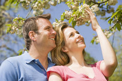 Couple standing outdoors holding blossom smiling Royalty Free Stock Image