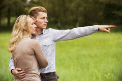 Couple standing outdoors and looking at something Royalty Free Stock Images