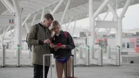Couple standing outside an airport with rolling suitcases. stock video footage