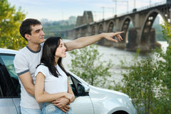 Couple standing outside their car in embrace. Young attractive couple standing outside their car in embrace pointing away Stock Image