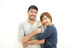 Couple standing over white wall. Portrait of Happy young Couple standing over white wall. Smiling and looking at camera royalty free stock images