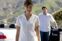 Couple standing beside parked convertible car on mountain roadside, focus on woman, smiling, portrait Stock Image