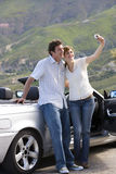 Couple standing beside parked convertible car on mountain roadside, woman taking self-portrait with camera. Couple standing beside parked convertible car on stock images