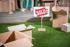 Couple standing on porch of new house and sold sign with cardboard boxes on grass Stock Photos