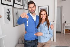 Couple standing at real estate sales office holding keys smiling happy royalty free stock photography