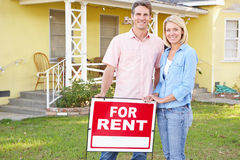 Couple Standing By For Rent Sign Outside Home. Smiling royalty free stock photo
