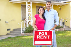 Couple Standing By For Rent Sign Outside Home. Smiling royalty free stock image