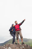 Couple standing on a rock looking up at the mountains Stock Photo