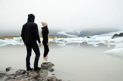 Couple standing on rocks glancing at glacier lake. Asian girl wearing woolly hat and winter boots and hooded men stand on rocks near the edge of a lake in the Royalty Free Stock Images