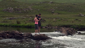Couple standing on rocks in the middle of a flowing river Stock Photo