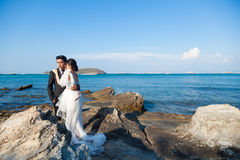Couple standing on the rocks by the sea. Royalty Free Stock Photography