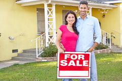 Couple Standing By For Sale Sign Outside Home stock image