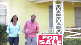 Couple Standing By For Sale Sign Outside Home stock video footage