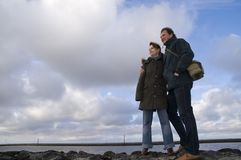 Couple standing on seawall Stock Photography
