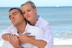 Couple standing on secluded beach. Couple standing on a secluded beach Stock Image