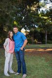 Couple standing in the shade. Of a large tree in the park Stock Photo