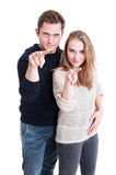 Couple standing showing watching you gesture Royalty Free Stock Photos