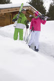 Couple standing in snow near lodge with skis Royalty Free Stock Photography