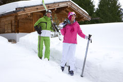 Couple standing in snow near lodge with skis Stock Images